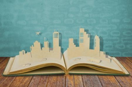 paper cut: Papier gesneden van steden met auto en vliegtuig op oud boek Stockfoto