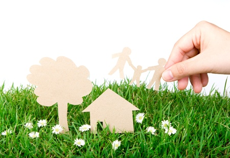ecology concept: Hand hold paper cut  of family over  fresh spring green grass