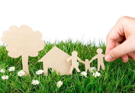 Hold cięte ręcznie papier z rodziną na świeżym wiosennym zielonej trawie