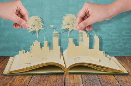Hand hold paper cut  of tree over Paper cut of cities with car and plane on old book photo