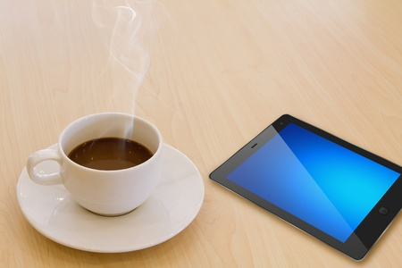 Touch screen device and cup of coffee photo