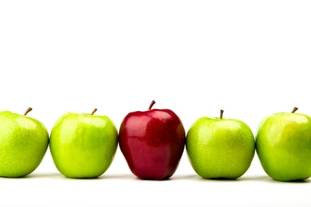 Red apple among green apples isolated on a white photo