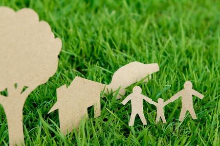 CiÄ™cie papieru z rodziny z domu, drzewo i samochód na Å›wieżym wiosennym zielonej trawie Zdjęcie Seryjne