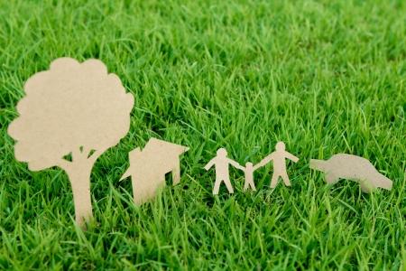 Cięcia papieru rodziny z domu, drzewo i samochód na świeże wiosny zielona trawa