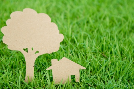 Paper cut of house and tree on fresh spring green grass photo