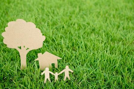Documento de corte de la familia con la casa y el árbol en primavera de la hierba verde fresca