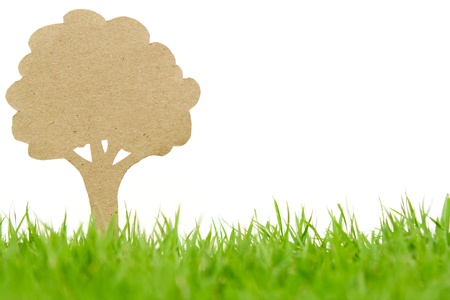 Paper cut of  tree on fresh spring green grass photo