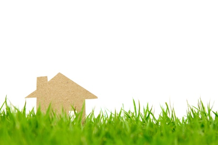 Paper cut of house on fresh spring green grass photo