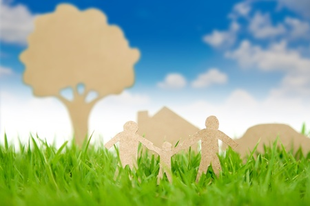 environment friendly: Paper cut of family with house and tree on fresh spring green grass Stock Photo