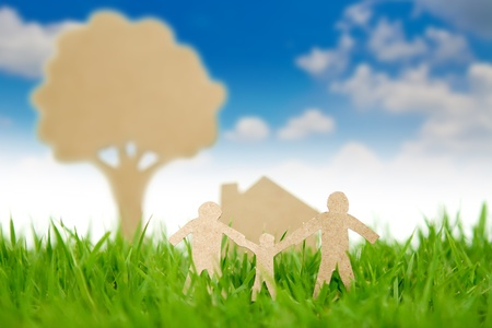 Paper cut of family with house and tree on fresh spring green grass photo
