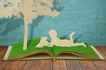 padres hablando con hijos: Corte del papel de los ni�os a leer un libro bajo un �rbol en el libro de la hierba de edad