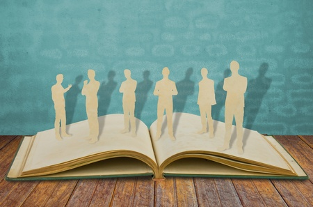 Paper cut of  business man  on old book Stock Photo - 13446091