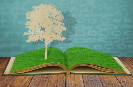 Paper cut of tree on old grass book Stock Photo - 13446113