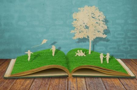 Cięcie papieru dzieci grać na starej książki trawy Zdjęcie Seryjne