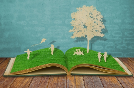 Paper cut of children play on old grass book photo