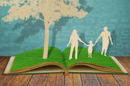 adulthood: Paper cut of family symbol under tree on old grass book