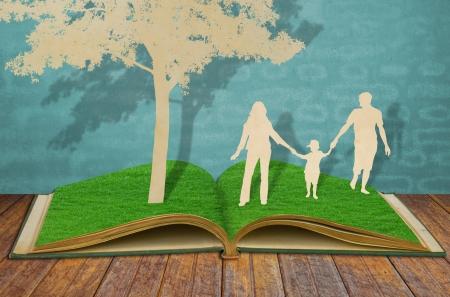 sotto l albero: Taglio della carta di simbolo della famiglia sotto l'albero sul libro erba vecchia