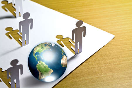 Paper cut of  people standing  with globe on wooden floor  (Elements of this image furnished by NASA) photo