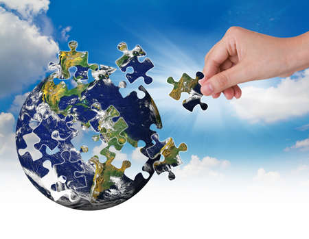 Business concept with a hand building puzzle globe Stock Photo - 13624295
