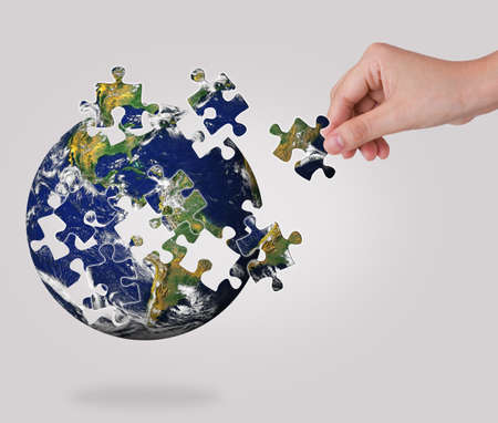 Business concept with a hand building puzzle globe photo