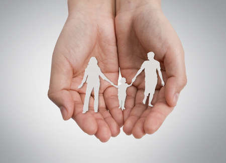 Hand with the paper cut of the family photo