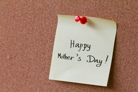Post it notes with word  Happy Mothers Day on a cork board photo
