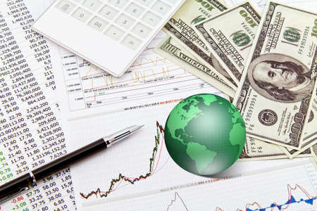Business graph,touchpad, pen,earth and dollars on table photo