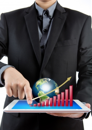 Business man holding the modern digital tablet pc with success growth chart and earth Stock Photo - 13783384