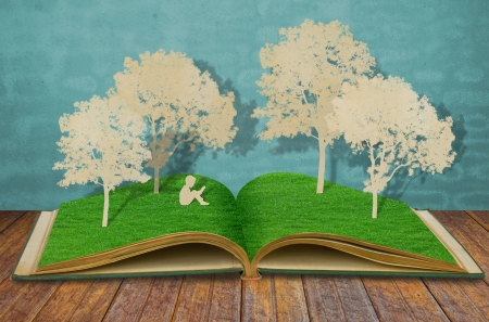 paper cut: Paper cut of children read a book under tree on old book Stock Photo