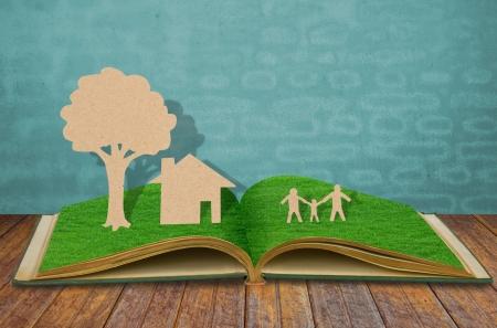 niños platicando: Documento de corte de símbolo de la familia en el libro de césped viejo Foto de archivo