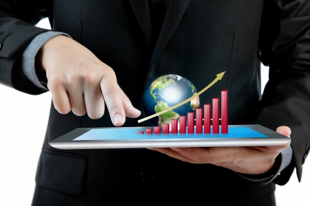 mobile marketing: Business man holding the modern digital tablet pc with success growth chart and earth (Elements of this image furnished by NASA)