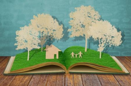 오래된 잔디 책에 가족 기호의 종이 컷 (집, 나무, 엄마, 아빠, 어린이)