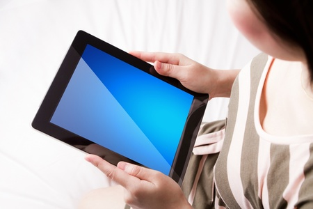 Woman reading the touch screen device photo