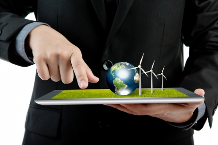 Business man holding the modern digital tablet pc with wind turbine and earth (Elements of this image furnished by NASA) photo
