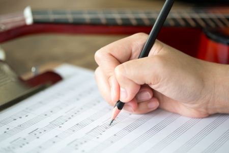Hand with pencil and music sheet Stock Photo - 14448330