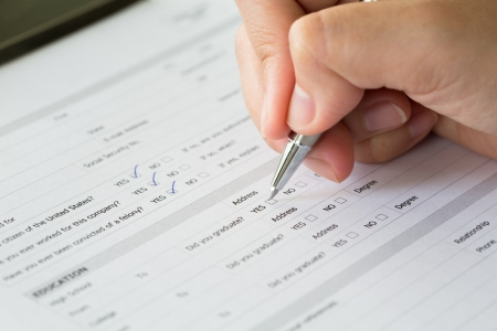 questionnaire: Hand with pen over blank check boxes in application form Stock Photo