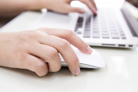 Closeup of business woman hand typing on laptop keyboard with mouse photo