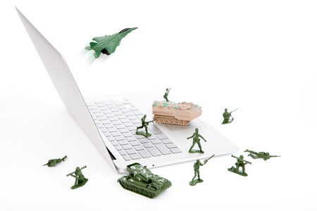 miniature people: Computer security concept :  soldiers,tank,plane  are guarding a laptop from viruses, spyware and hacker Stock Photo