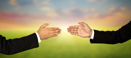 Two business male hands about to shake hands, over white background photo
