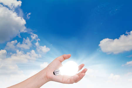 Women hand with lamp bulb against the blue sky. Stock Photo - 14930792