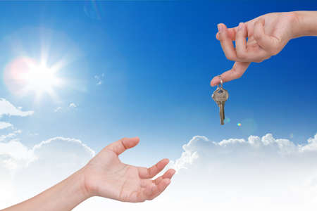 Human hand with key and blue sky photo