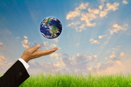 Eco concept : Hand hold globe in bubbles against the sun and the blue sky photo