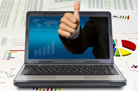 thumps up: Business hand thumps up come out of the laptop screen on financial Graphs