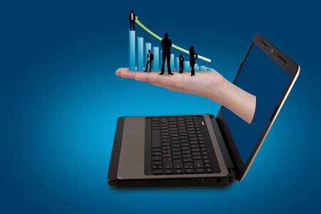 A Hand reaches out of an Laptop with silhouette people and graph photo
