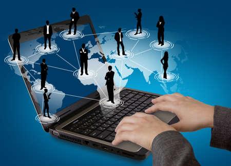 trabajo social: Concepto de redes sociales: Ordenador port�til con la red social on world map
