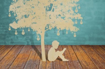 under the tree: Corte del papel de los ni�os leen un libro bajo el �rbol de la bombilla