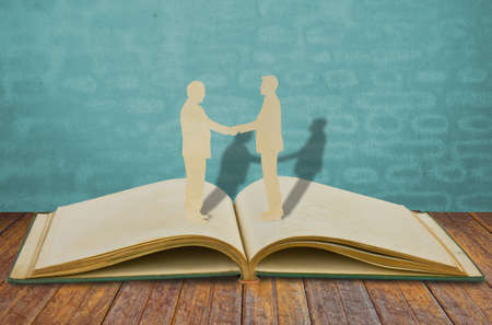 colaboracion: Corte del papel del hombre de negocios de dos estrechar la mano sobre el libro antiguo