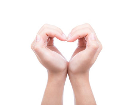 Heart shaped from woman hand isolated over white background photo