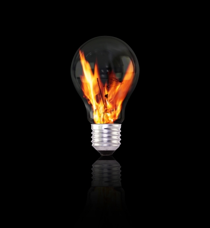 light bulb with fire on black background photo