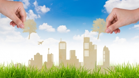 realty: Woman hand put Paper cut of tree over  city and grass with blue sky Stock Photo